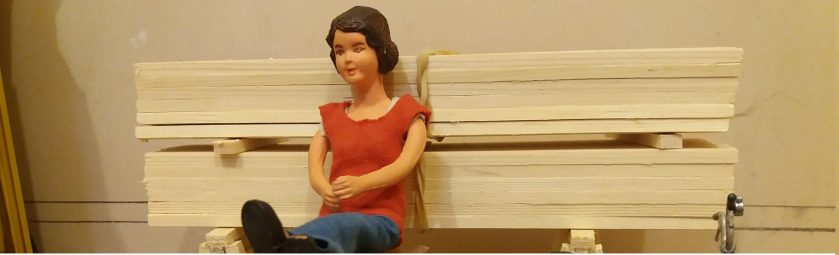 Harriet Board seated on a workbench leaning back on a stack of timber.