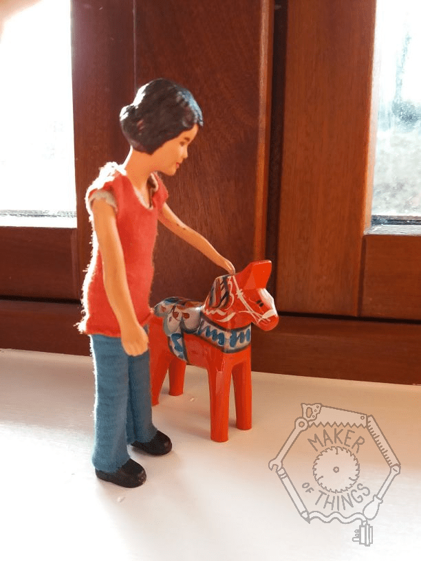 Harriet is petting a small painted wooden horse. The horse is red with bands of blue and white patterns. It is about half Harriet's height.