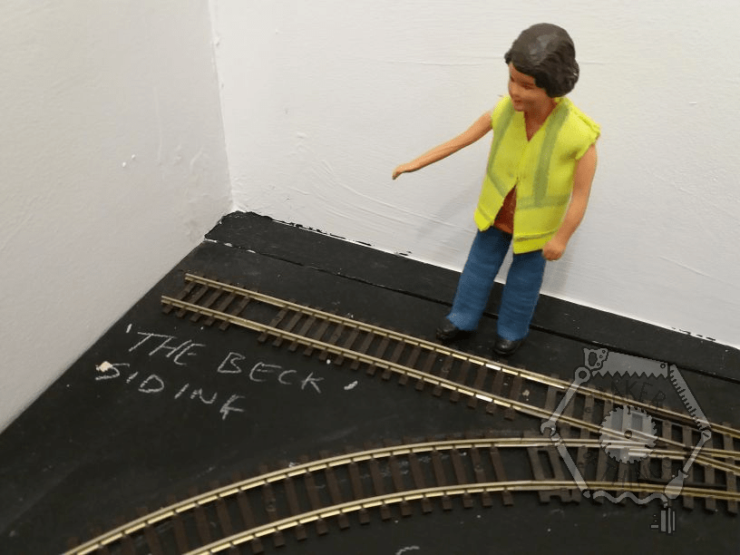 Harriet is pointing at the short straight siding going into the corner of the garden railway.