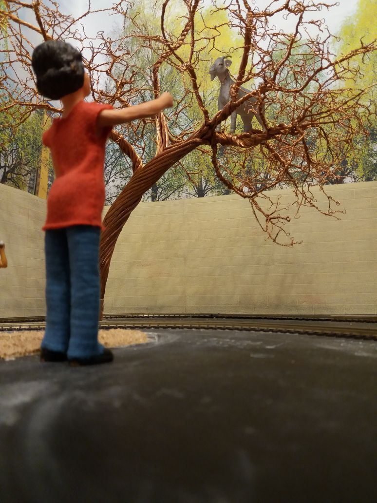 Harriet is looking up at a tree on the garden railway. There is a large goat in the tree!