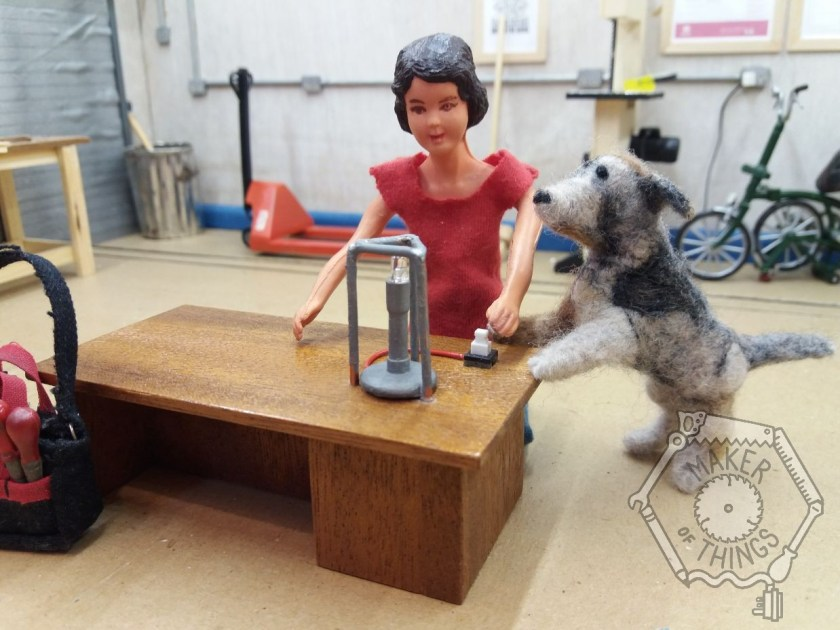 Harriet has the bench right way up and has installed a switch in the bench top. There is a Bunsen burner and tripod on the bench. The Bunsen burner gas pipe is now a red wire going to the switch. Monty is pawing the switch.