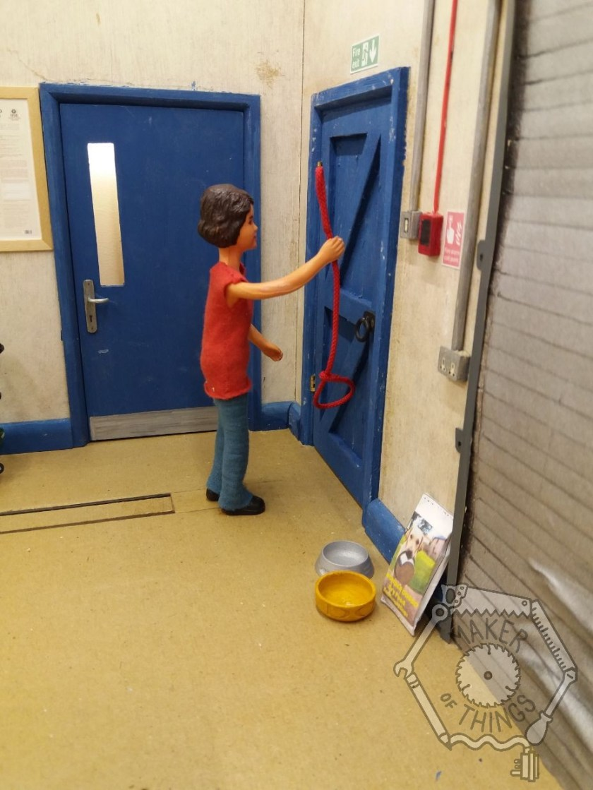 Harriet is in her workshop looking at the door. She is holding the dog lead up to see where a hook could go to hang it up. There is a dog food and water bowl on the floor by the door.