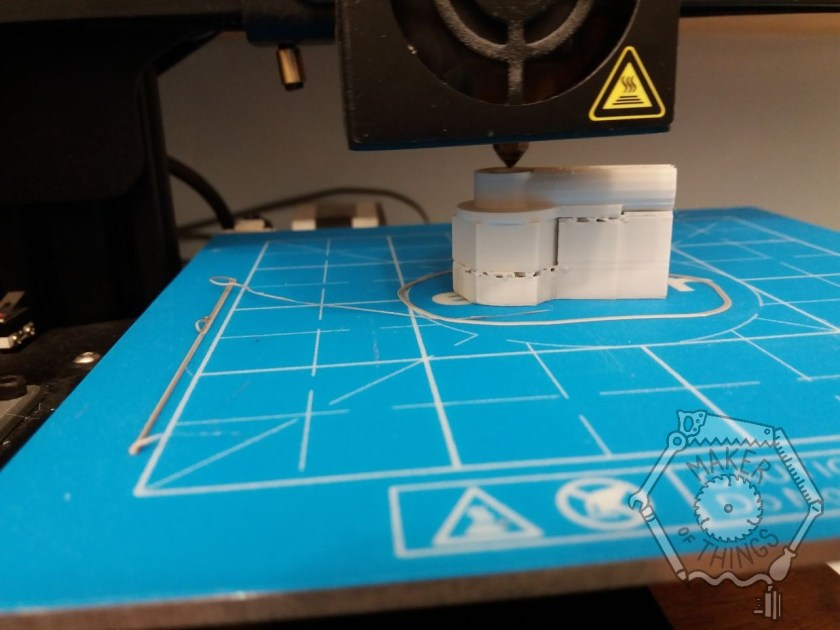 A white 3D print in progress on a blue print bed with the black print head above.