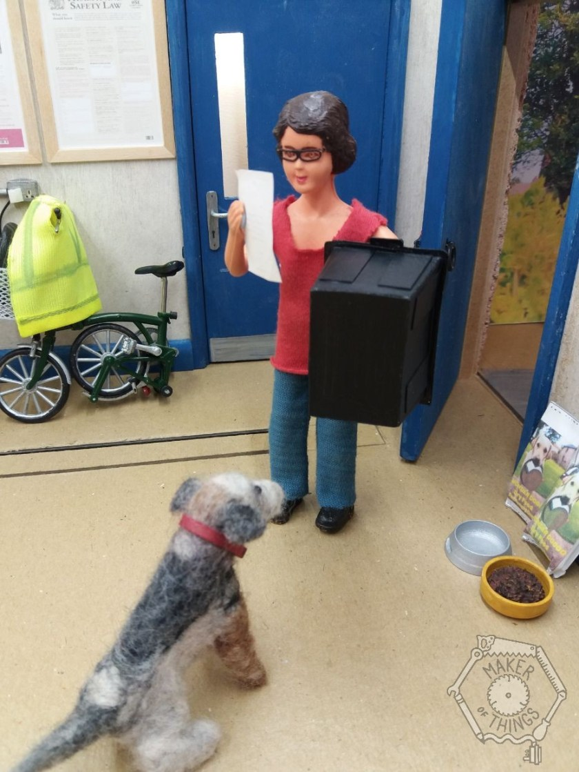 Harriet is in her workshop holding a letter in her right hand, and a large black plastic box in her left hand. Monty Dog is watching with interest.