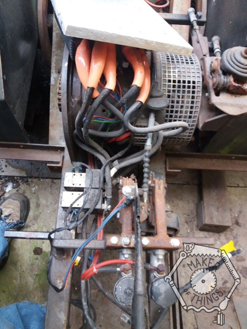 The wooden cover panel under the seat has been removed showing the electric motor and some very big cables with orange ends connected to the speed controller.