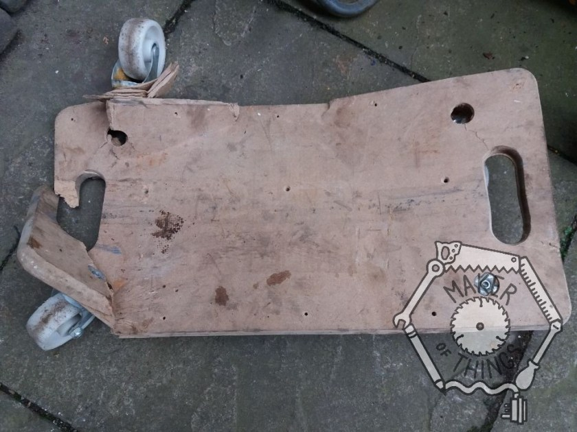 An MDF trolley that has been crushed, the wheels have broken off and the MDF board is in pieces.
