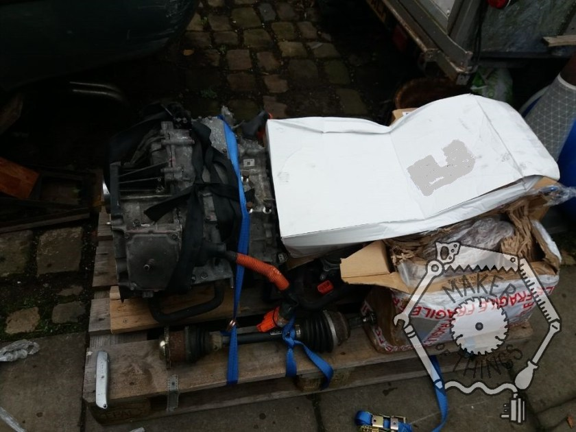 The stuff on the pallet with the clear pallet wrap removed. There is a gearbox on the left, a drive shaft, and a pile of boxes.