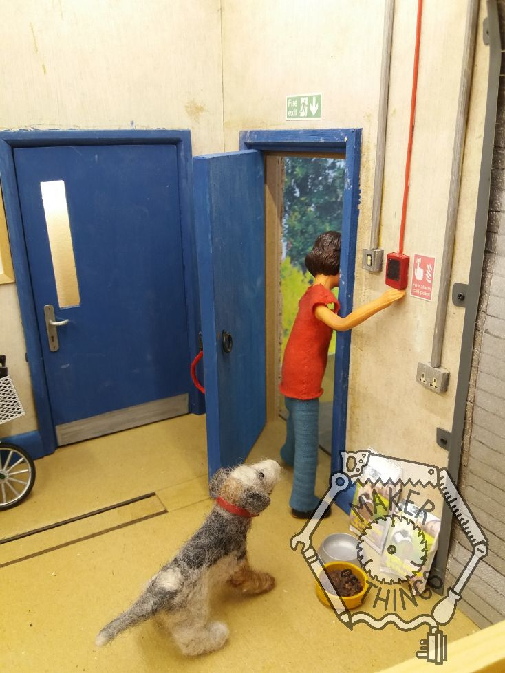 Harriet is cautiously peering around the edge of the open workshop door trying not to be caught looking while Monty Dog looks on.