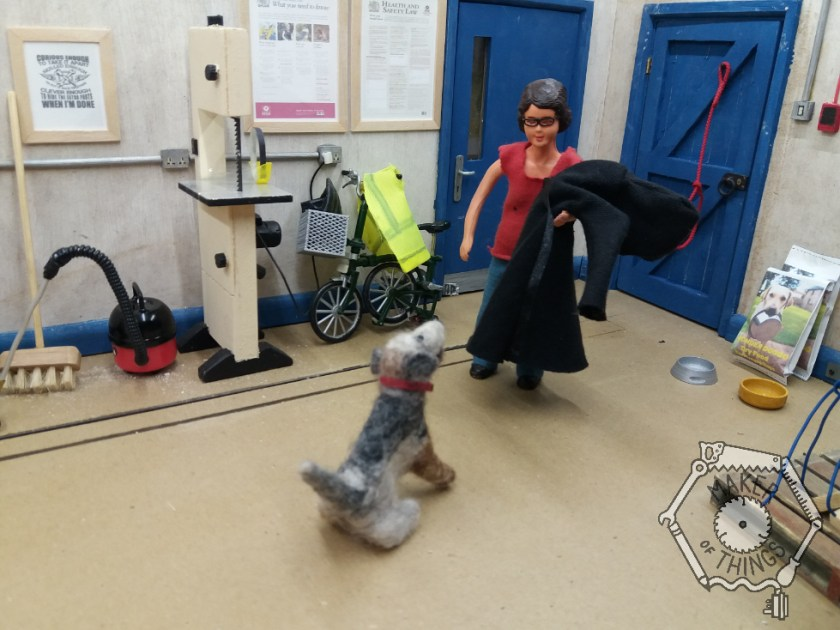 Harriet is back in the workshop. She has taken her coat off and is carrying it draped over her arm.