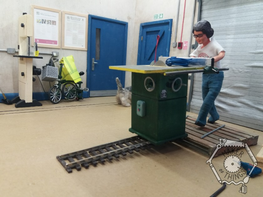 Harriet is easing the table saw onto the railway track ramp while standing on the pallet.