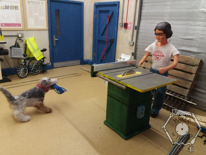 The table saw is now completely on the ground and Harriet is standing at one end, by the big roller shutter, as if using it. She has given the blue rope to Monty Dog to play with.