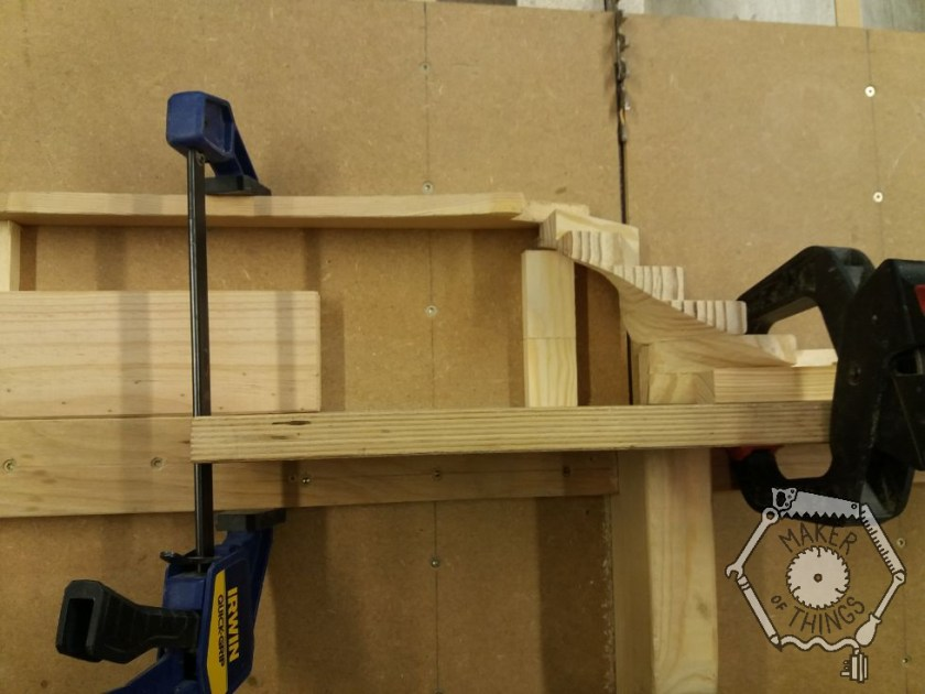Overhead view of the stair winder cl;amped over the table saw for cutting.