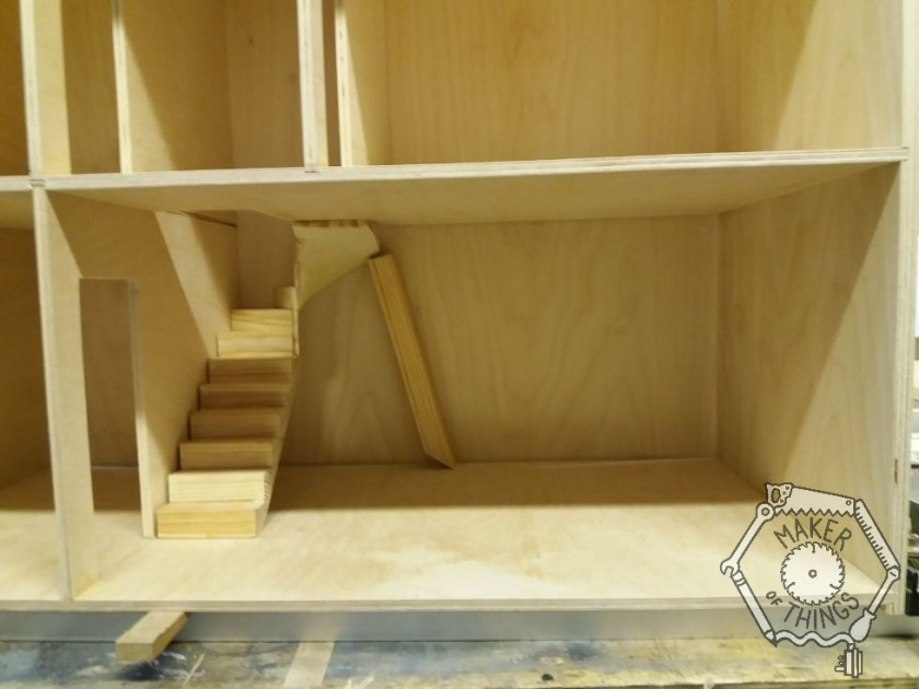 A close up of the open plan room with the staircase set into it and a stick holding the top end up.