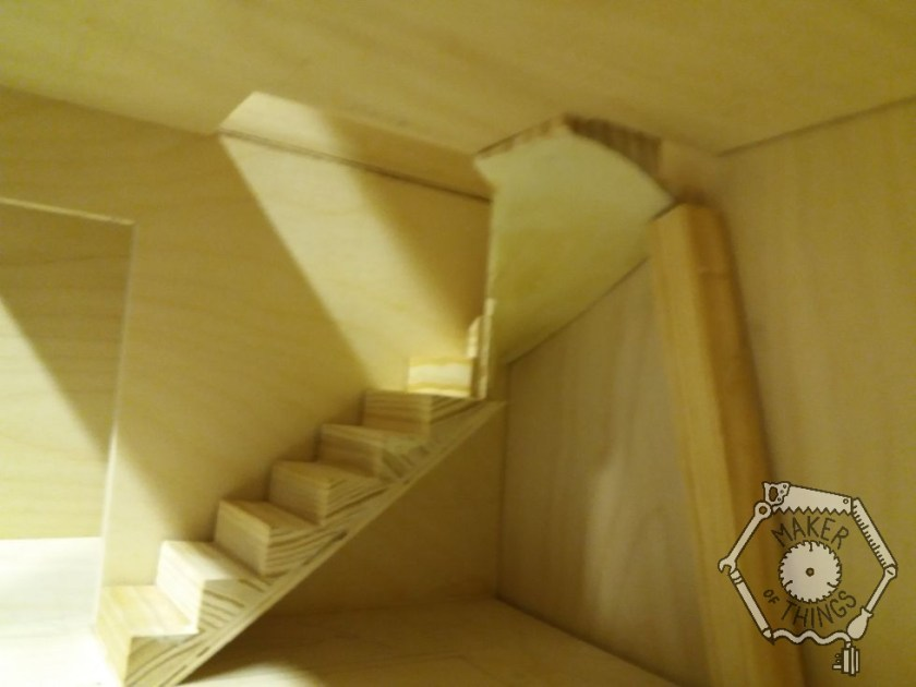 A close up side view of the stairs and winders, with a stick prop holding it up, in the back of the living room