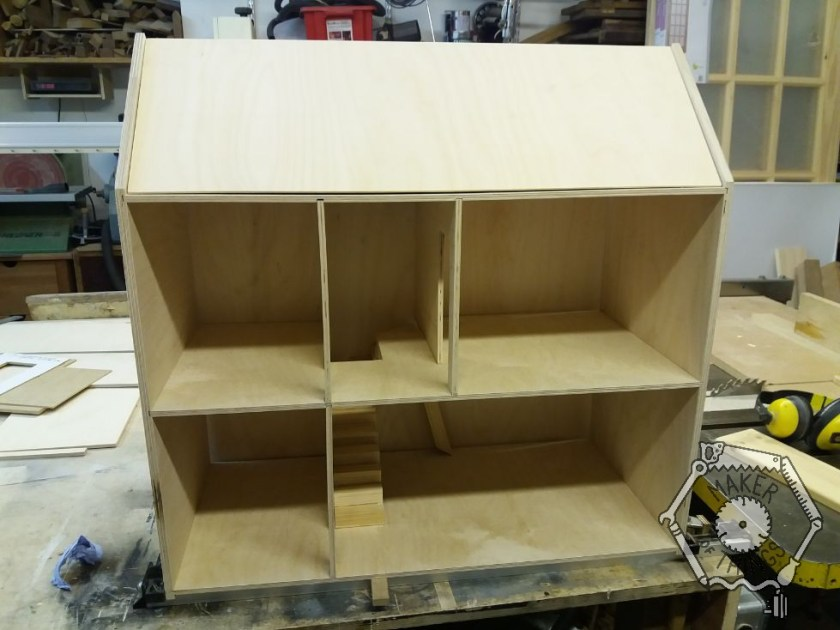 An overall view of the dolls house with a pitched roof.