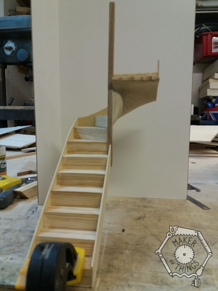 Front view of the stairs and winders with a tall newel post fitted, and the stringers on each side of the treads fitted.. The stair is clamped to the edge of the work bench.