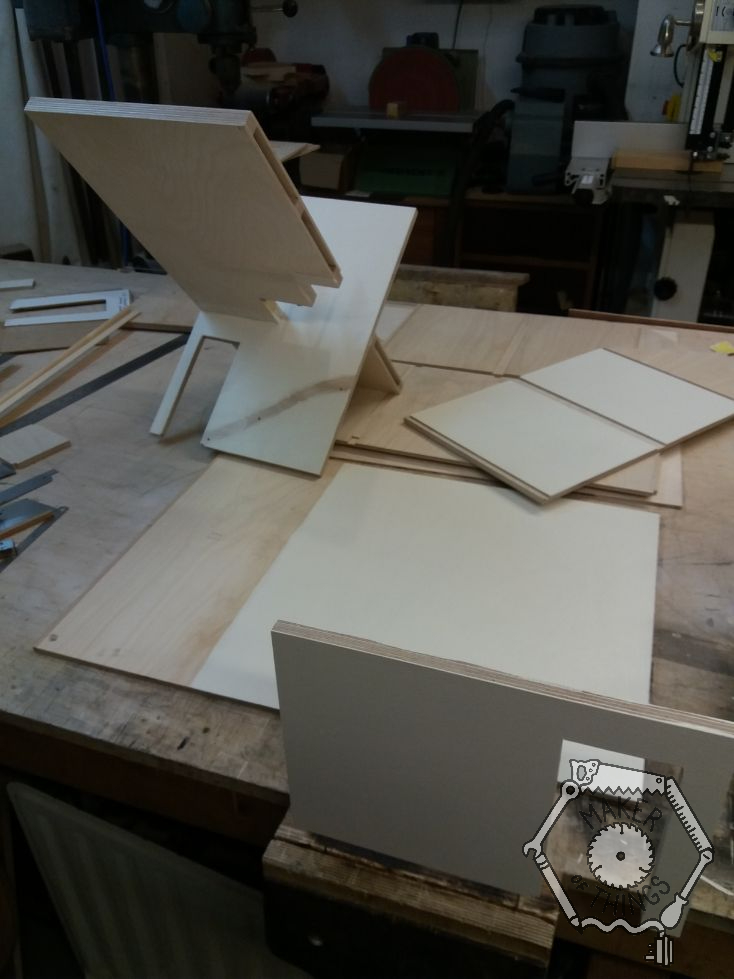 Sections of plywood dolls house walls and floors on the bench, part painted.