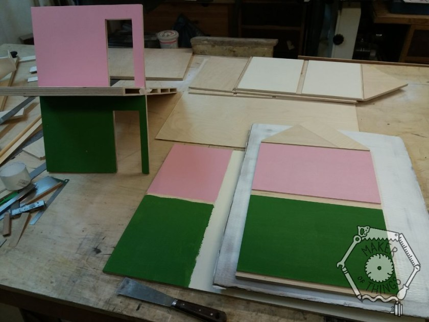 Sections of dolls house walls and floors on the bench. the bathroom walls are painted pink and the kitchen is in dark green.