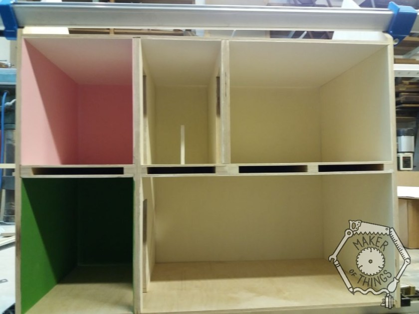 Front view of the dolls house dry assembled showing the rooms in colour, magnolia, pink, and green.