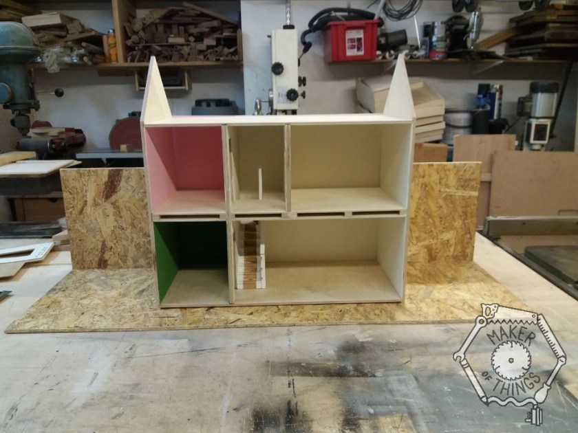 A distant view of the dolls house on the workshop bench placed on some OSB for the ground and backdrop.