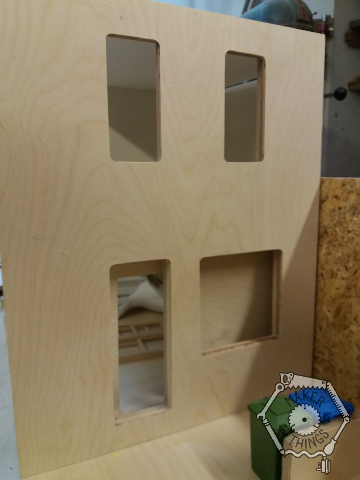 Front of the house with windows and door cut outs with rounded corners from the router cutter.