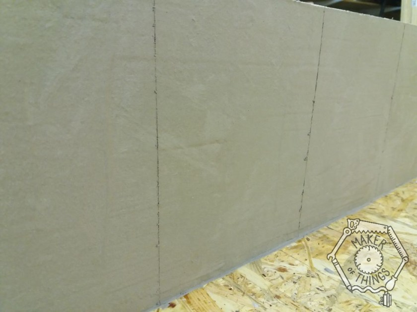 An oblique view of the grey plastered concrete wall with a good view of the vertical joint lines in the panels.