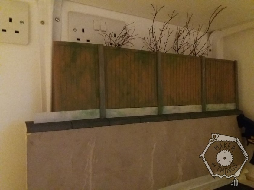 The fencing for the front of the house back drop with some twiggy 'bare trees' peeping over the top.