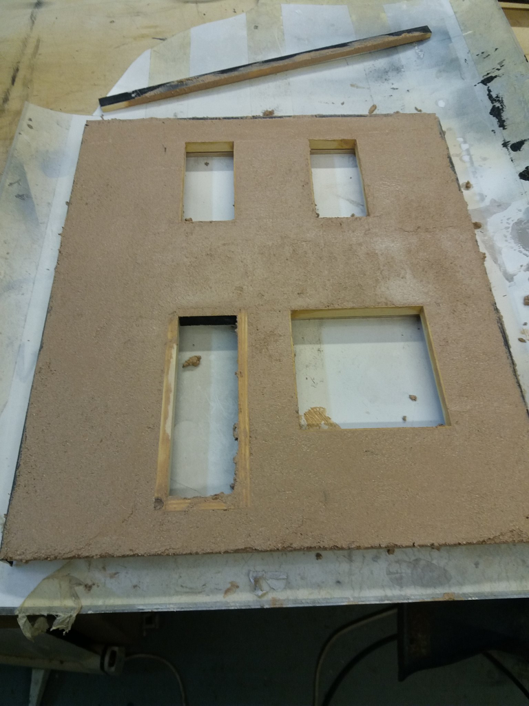 The front wall of the dolls house on the work bench covered in wet bonding plaster.