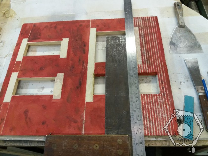 The front wall of the house with a square and a steel rule being used to scribe the horizontal brink courses.