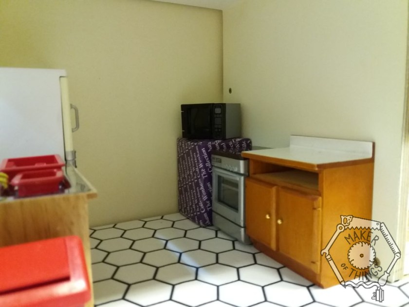 The opposite wall of the kitchen showing a random box in the corner with a microwave on top, a silver electric cooker, and a two door cupboard.