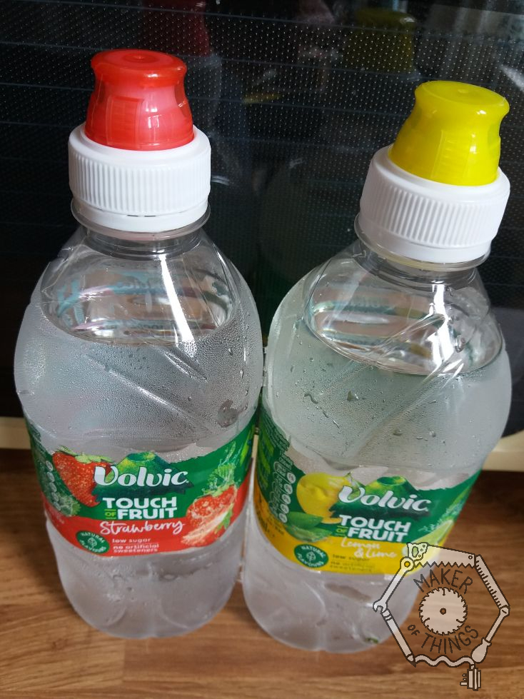 Two bottles of Volvic flavoured water with drinking nipple screw caps. One has a translucent red cap and the other has a translucent yellow cap.