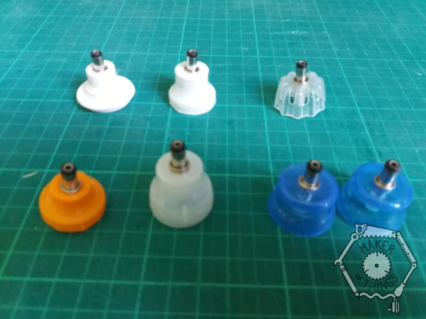 Seven bottle cap lampshades with barrel jack blugs and LEDs installed. Two are blue translucent, one is white translucent, two are plain white in different shapes, one is orange, and one is a crinkly shaped clear cap.