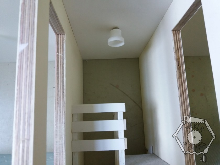 A white 'bell' shaped drinks bottle nipple installed as an upstairs landing ceiling light.