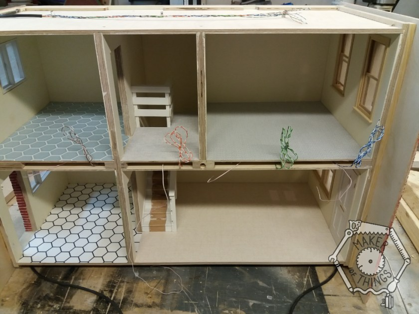 The front view of the dolls house showing two loops of multi core cable coming out from the base.