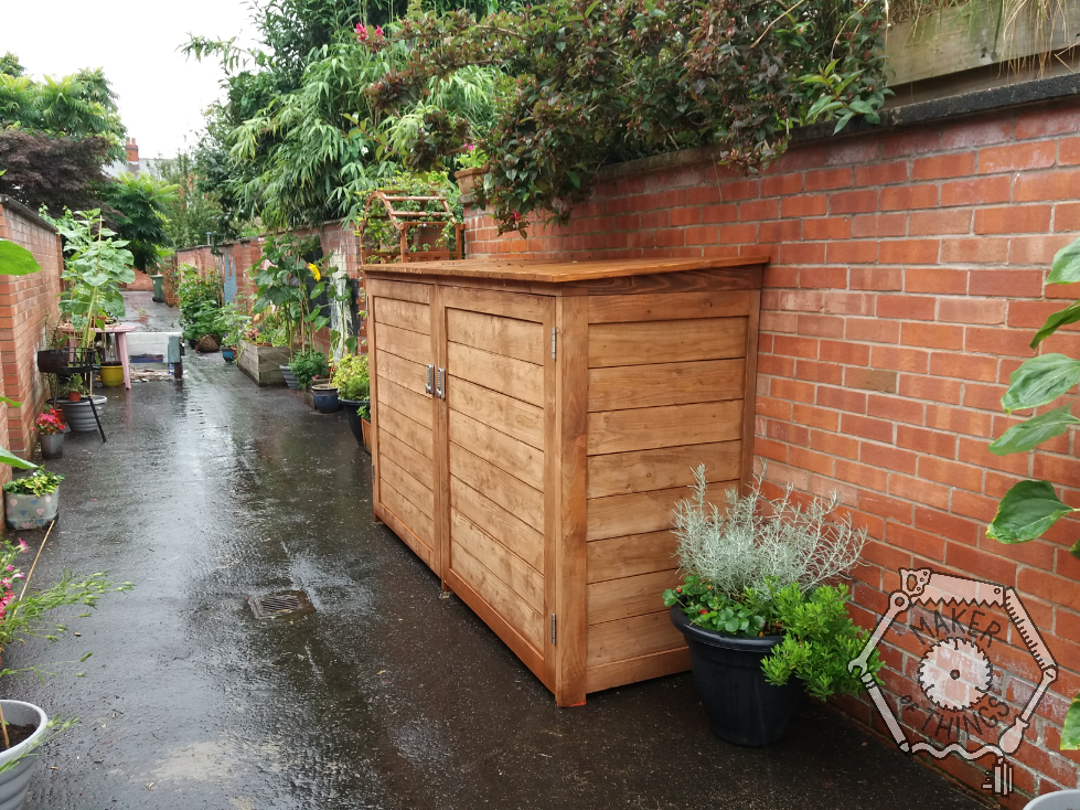 The completed bin store fixed to a wall in a clean and tidy back alley. There are plants around it.