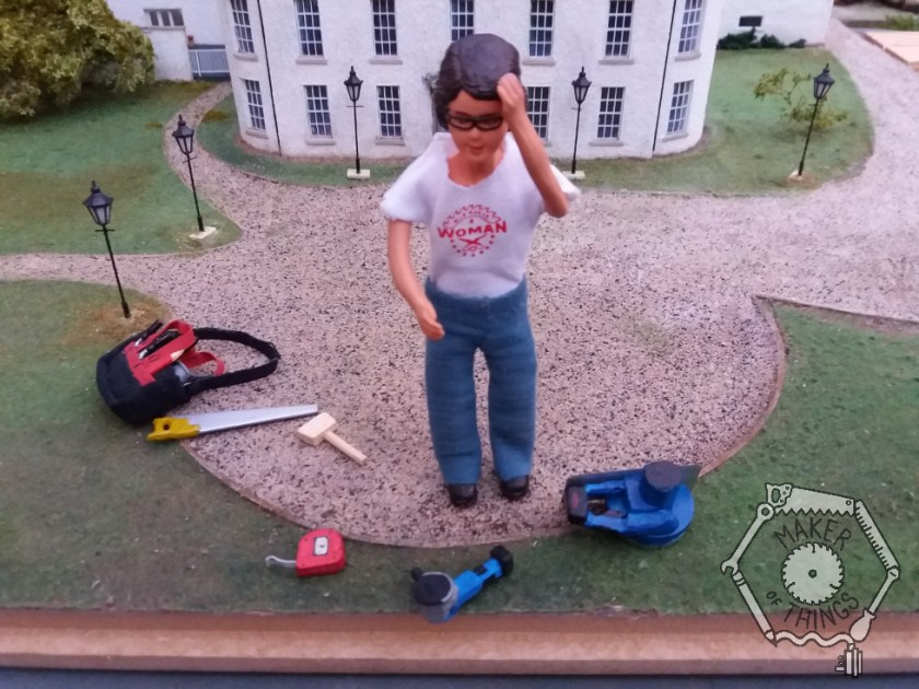 Harriet is standing in front of the house and looking at the edge of the wooden plinth that the model house is built onto. She has a tape measure, a mallet, a hand saw, an angle grinder, and a circular saw out of her tool bag and is scratching her head as she thinks about the job.