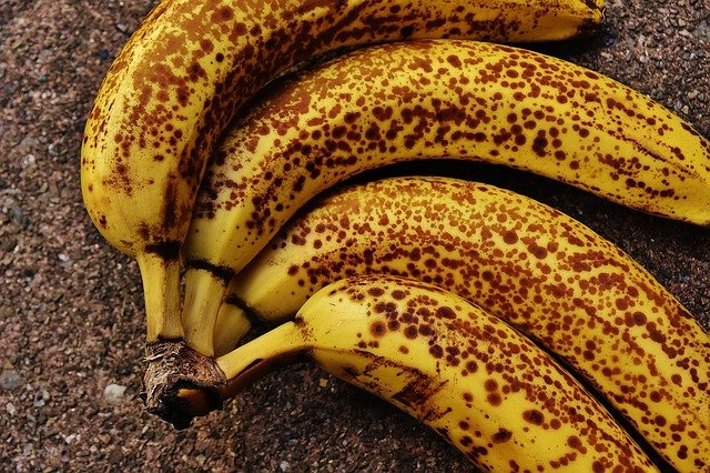 Four very ripe bananas with brown spots.