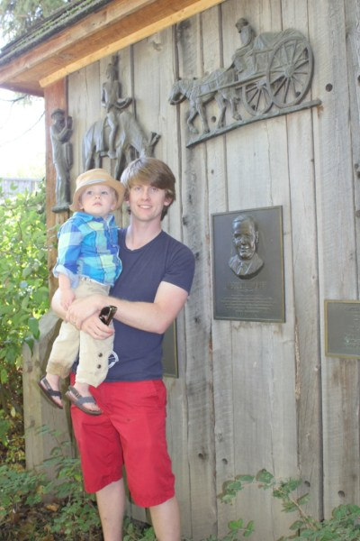 Brady & Carson in front of a memorial dedicated to Brady's Grandpa as one of the founders of Fort Edmonton Park.