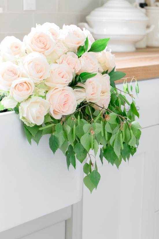 soft pink roses, green leaves in farmhouse sink