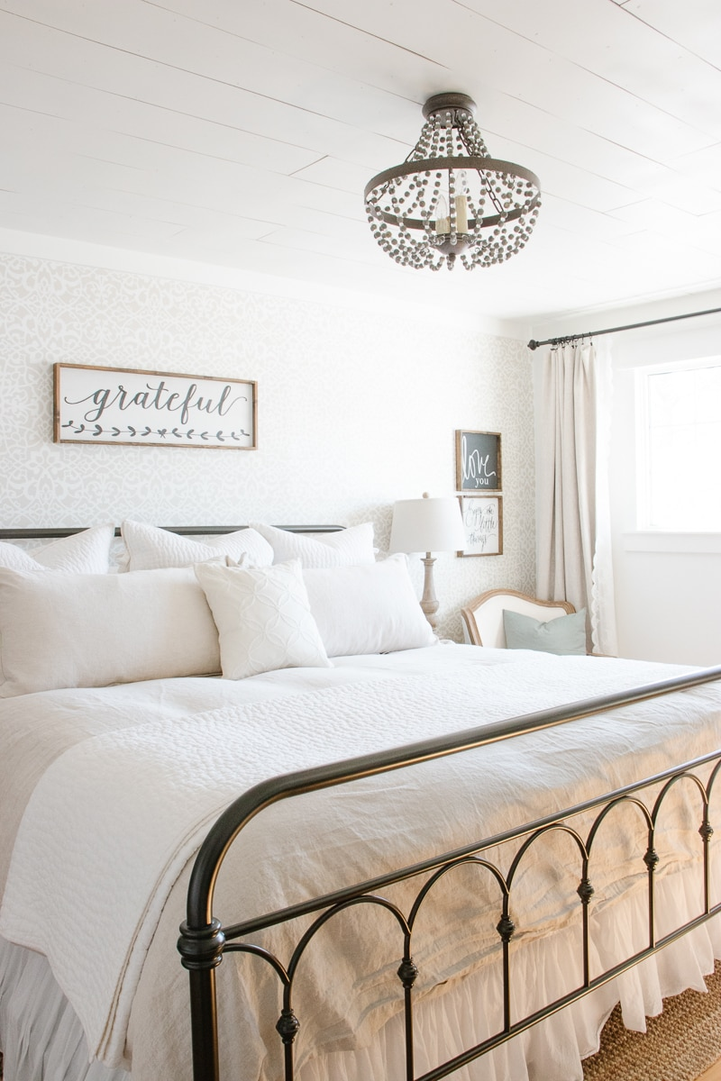 iron bed, white bedding, linen bedding, stencilled wall, shiplap ceiling