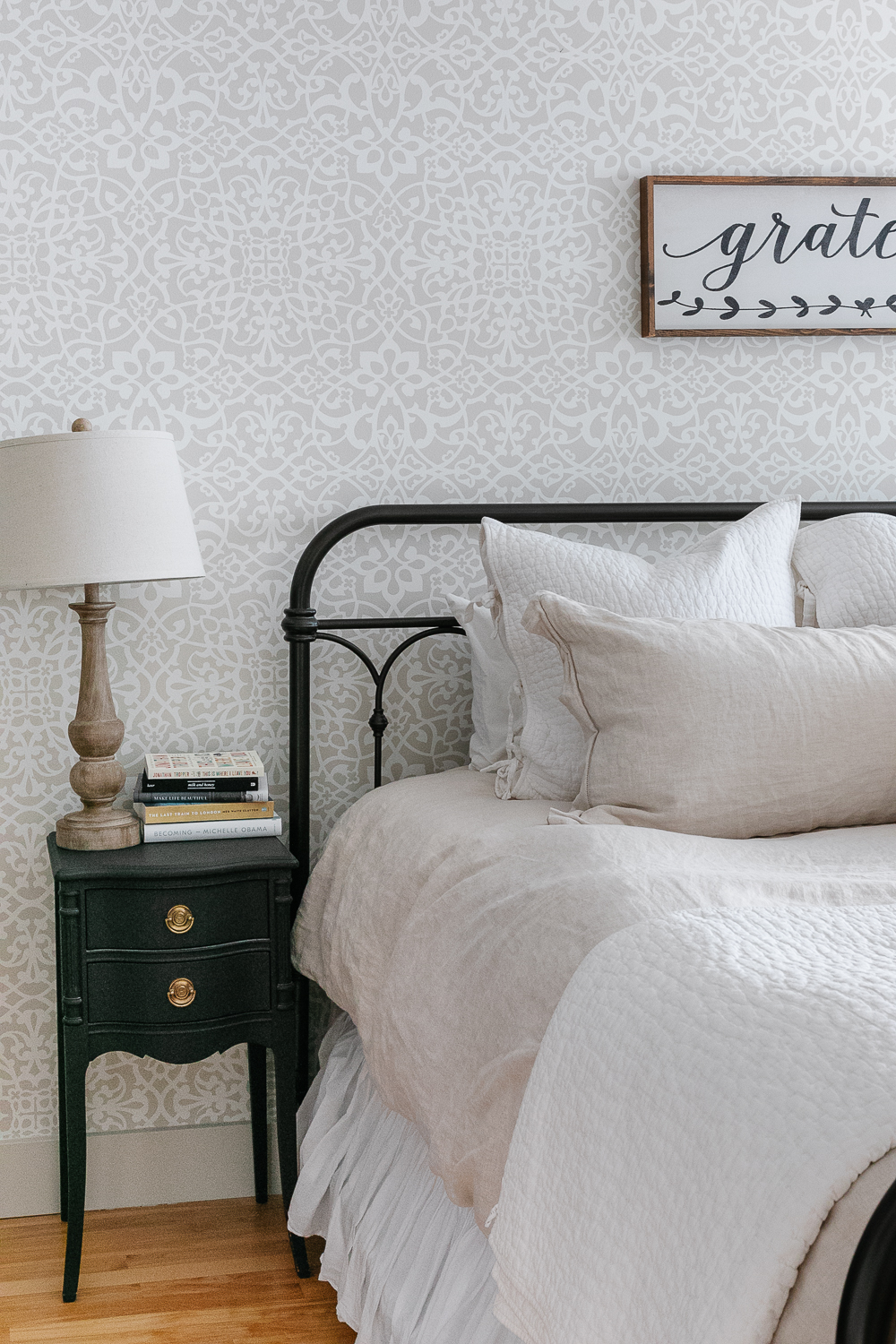 book stack, wood lamp, iron bed, black night table, wallpaper, stencilled wall, linen bedding