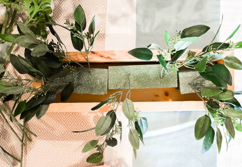 See how I made a simple wooden box to use as a centerpiece and filled it to the brim with lovely green and neutral flowers. It's the perfect farmhouse neutral floral centerpiece that can be used in all seasons!