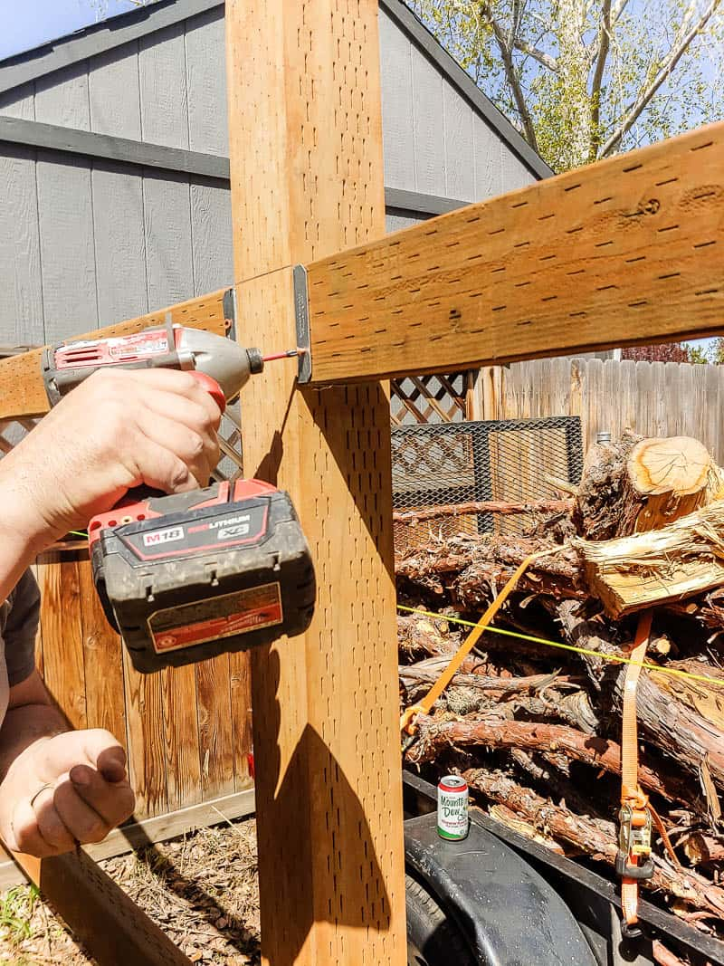 shows someone drilling the bracket for fence rails