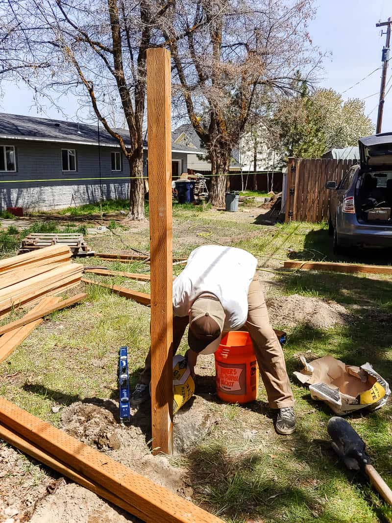 shows a man leveling out the fence post in the cement