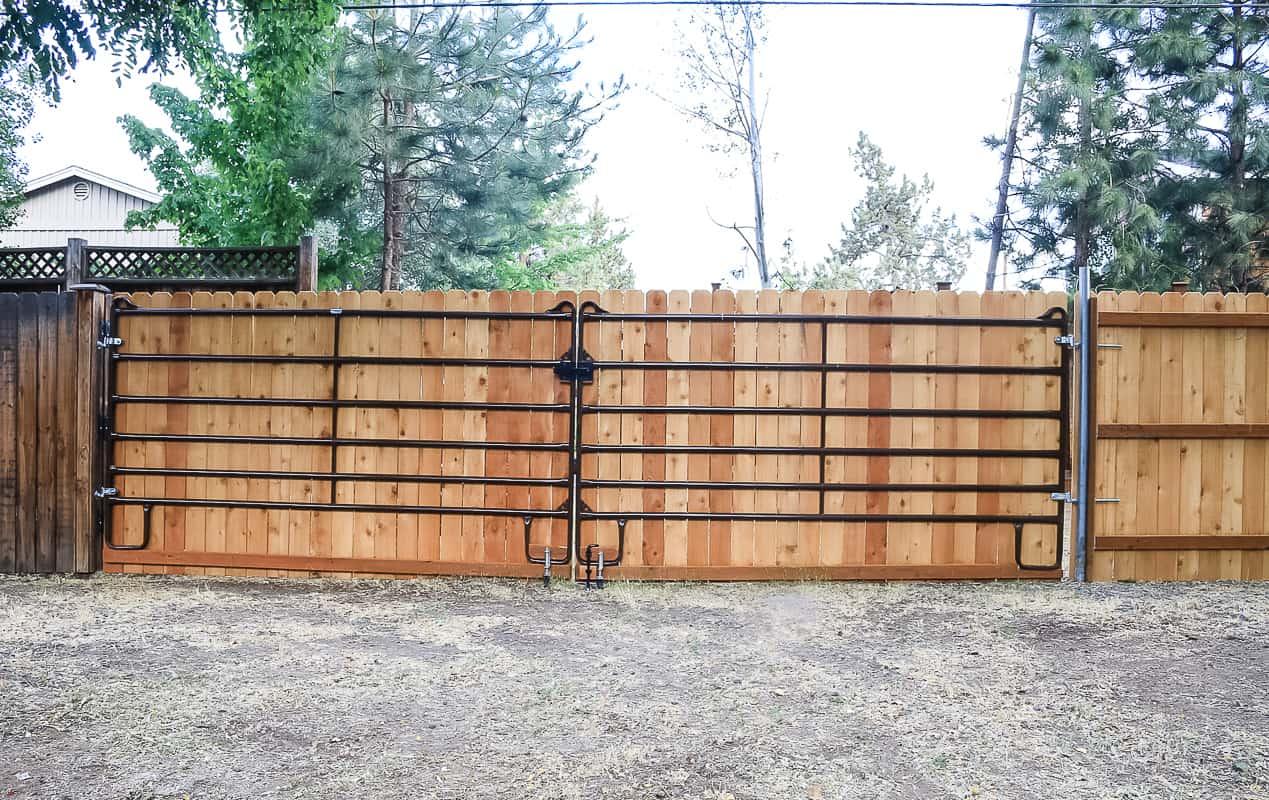 large metal gate in backyard on wood fence
