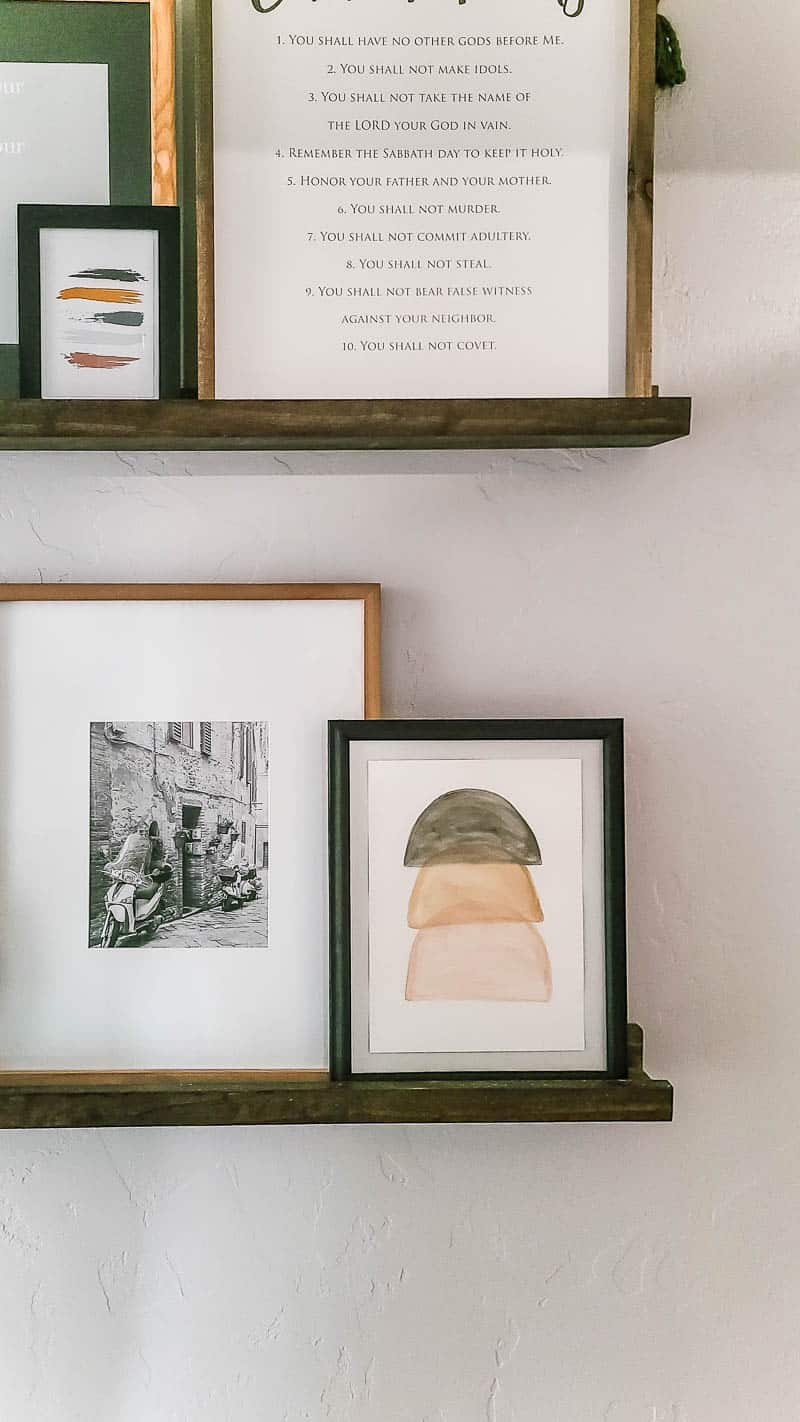 neutral boho wall art on shelves beside a photo frame