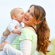11640429 - laughing young mother hugging her baby in hands outdoors