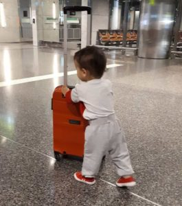 Baby carries suitcase in airport