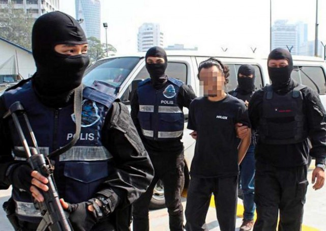 A Malaysian suspected of being involved in terrorism related activities is taken away by police. Pic by mole.my