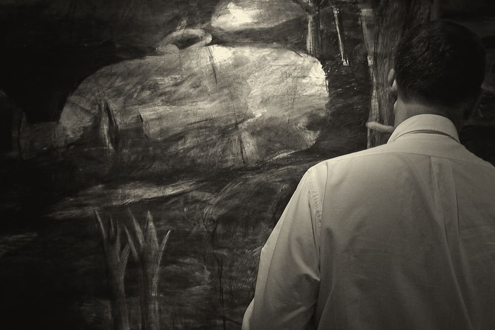 Malcolm Moran at work on large charcoal drawing of reclining man asleep